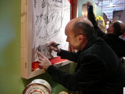 Laurent signant un tablier dédicacé par les grands chefs passant sur le salon
